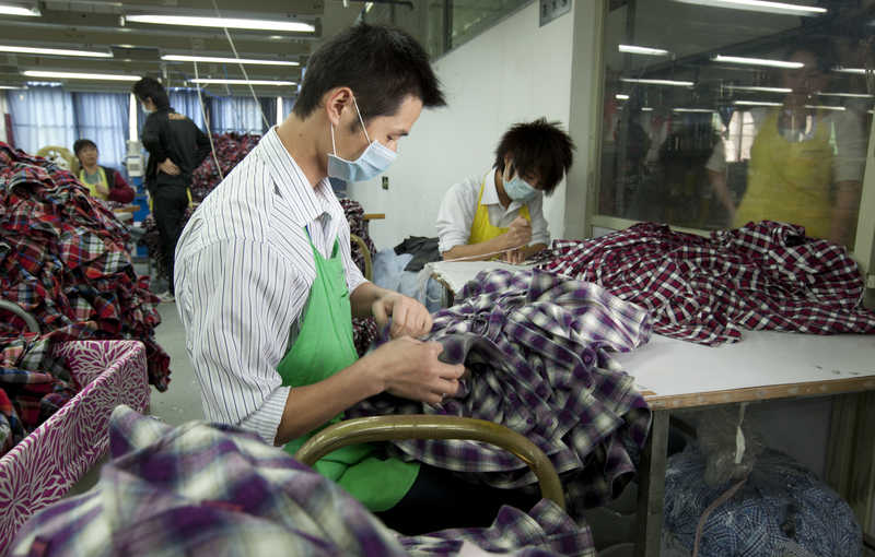Workers process shirts at Lever Style Inc. factory in Shenzhen