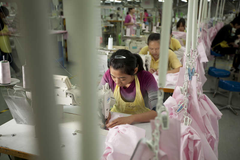 Workers assemble shirts at the Lever Style factory in Shenzhen