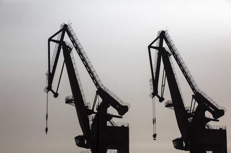 Cranes stand idle at the Port of Shekou in Shenzhen