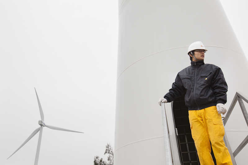 A China Resources New Energy Group employee stands at a wind turbine in Shantou