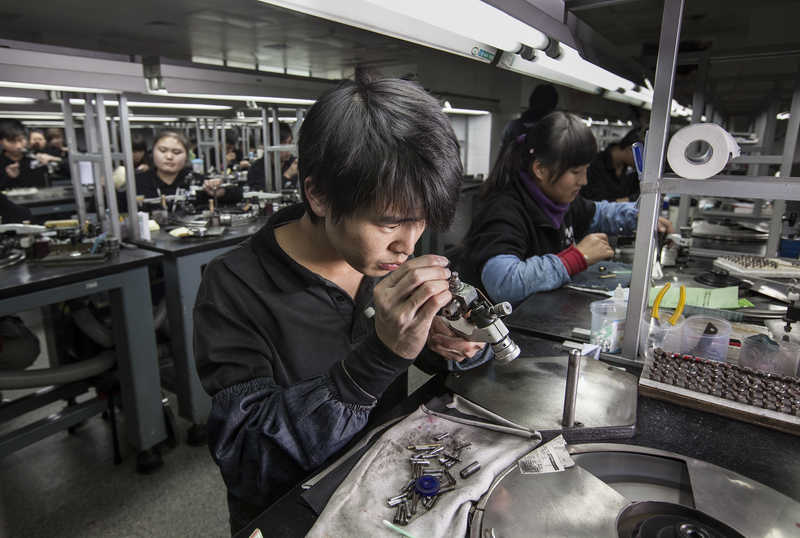 Workers polish diamonds at Guangzhou Mickey Weinstock & Co factory