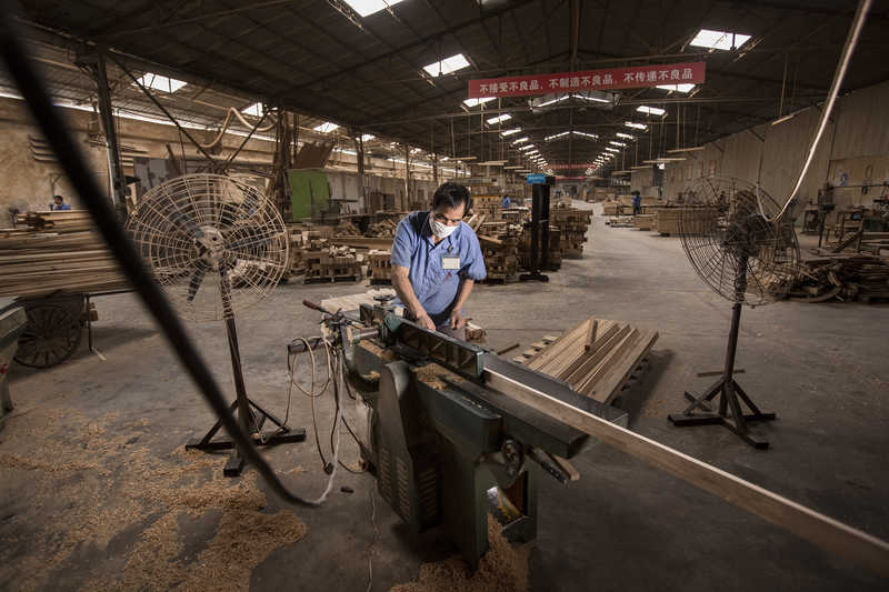 A worker operates a planer at a factory in Panyu