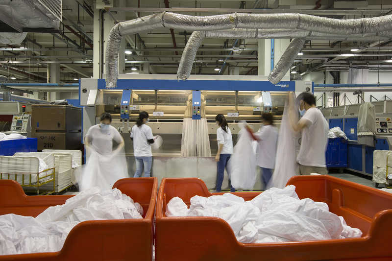 Workers launder hotel linens at Seng San Enterprises in Coloane, Macau, China.