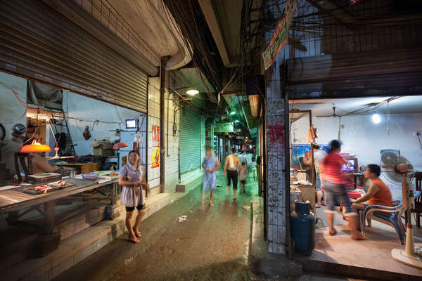 People walk through a crowded alleyway in Yuancun village