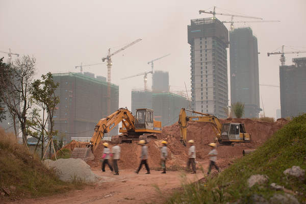 Workers walk past construction equipment in Pazhou, Haizhu District