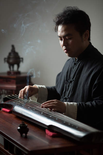 A musician plays the guqin at his studio across the street from Kaifu Temple