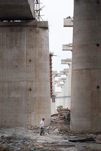 A man walks under new construction for an elevated roadway and high speed rail line in Hainancun, Liwan