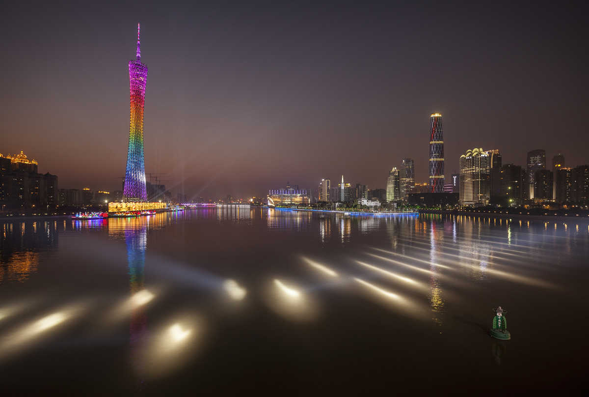 Photograph of the Guangzhou Tower, IFC Tower and other Tianhe District buildings flanking the Pearl River at dusk.