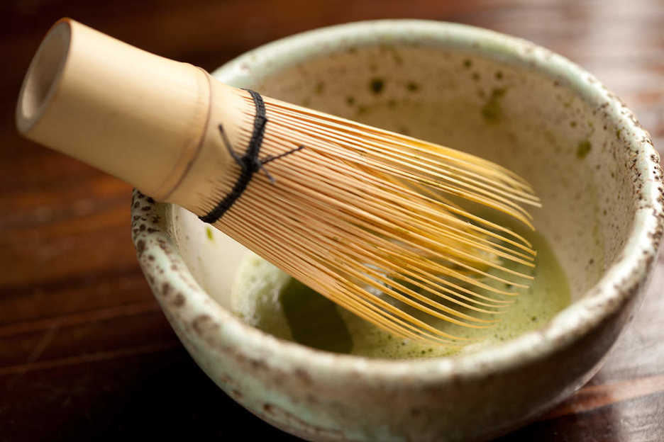 Mixing matcha with a chasen, a bamboo tea whisk.