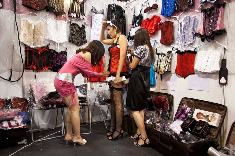 An performer at the Asia Adult Expo tries on a new outfit at a trade fair booth.