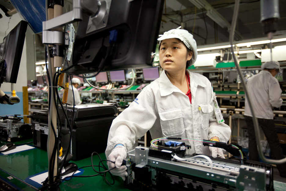 A Foxconn worker tests a computer printer along the assembly line in Shenzhen
