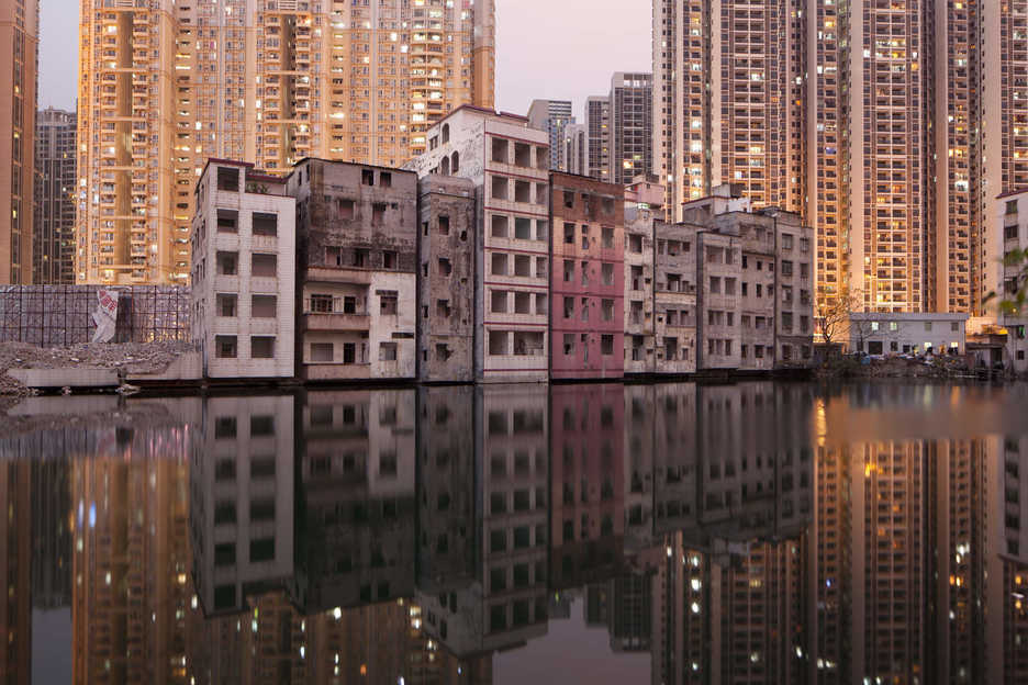 A row of partially-demolished apartment buildings line a lake in Tianhe District, Guangzhou, China