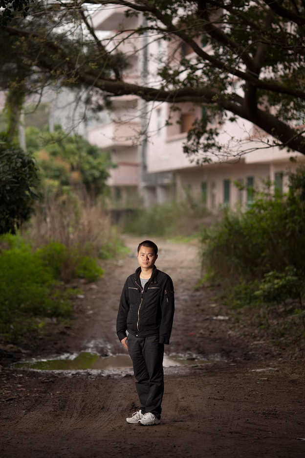 Zhan Dexin poses near his missing son's school in Huizhou, Guangdong Province, China