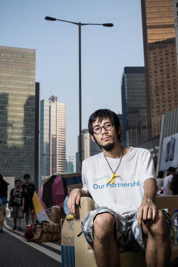 Pro-democracy protester poses on appropriated furniture in Central, Hong Kong
