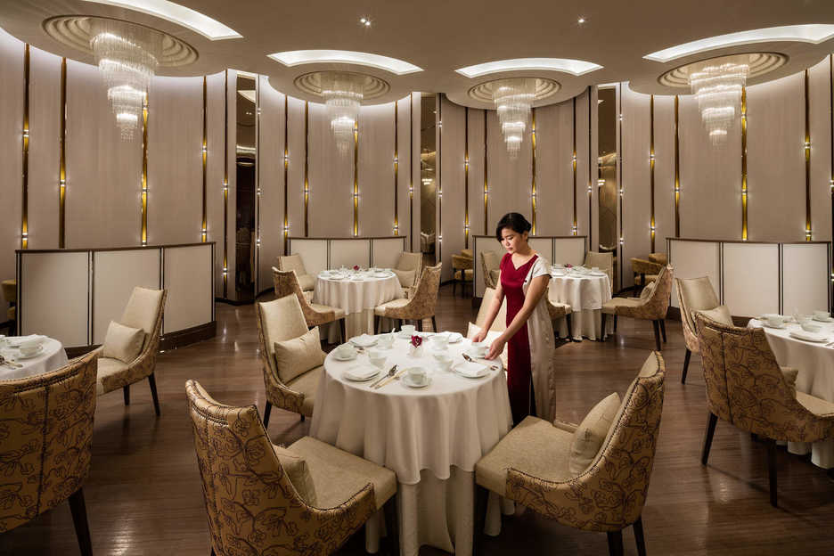 A waitress poses at a table in the Man Ho restaurant in Macau