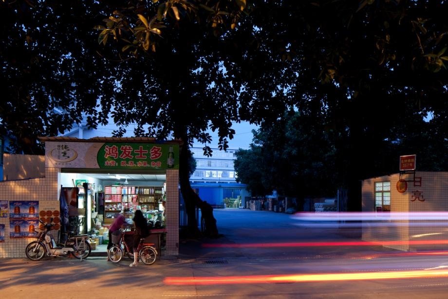 woman with electric bicycle at street-side convenience store in Baiyun district
