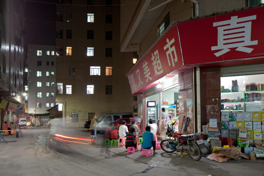 People watch a TV set outside a shop in Yongtai Village