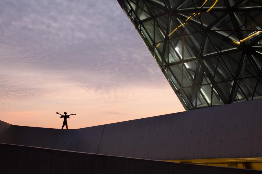 A statue is seen at dusk on a balcony at the Guangzhou Opera House designed by Zaha Hadid