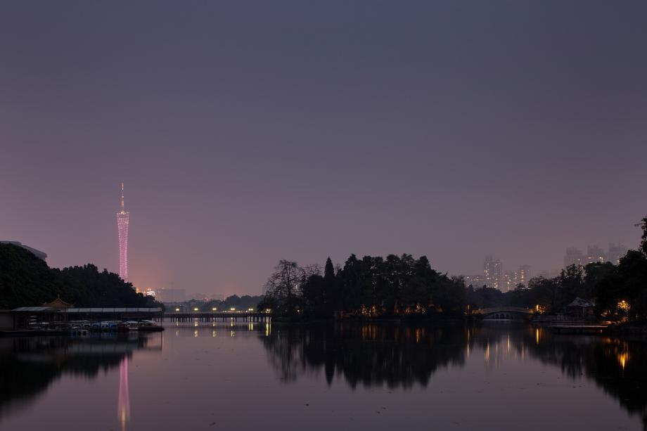 Dongshanhu Park and the Guanghou Tower are illuminated at dusk in Guangzhou, China.