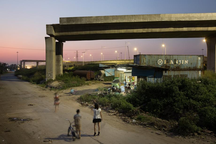 People stand near an unfinished elevated roadway in Foshan, China.