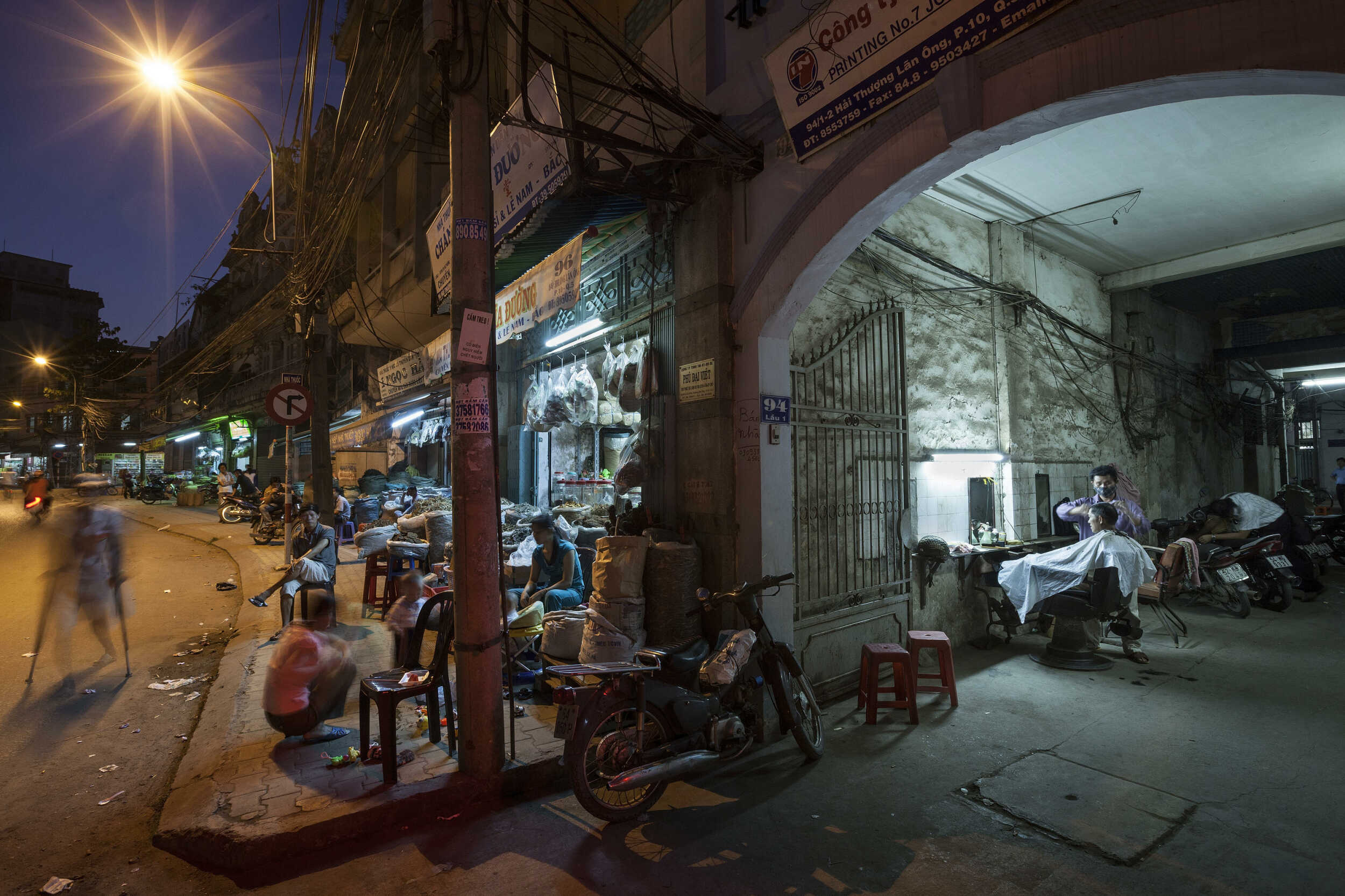 Editorial photograph of an alleyway barbershop along a street lined with traditional herb shops in Cholon, Ho chi Minh City, Vietnam.